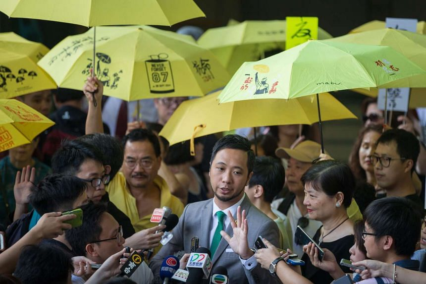 Pro-democracy activist Ken Tsang (centre) speaks to members of the media after his trial at the Kowloon City Magistrates Court in Hong Kong, on May 30, 2016.
