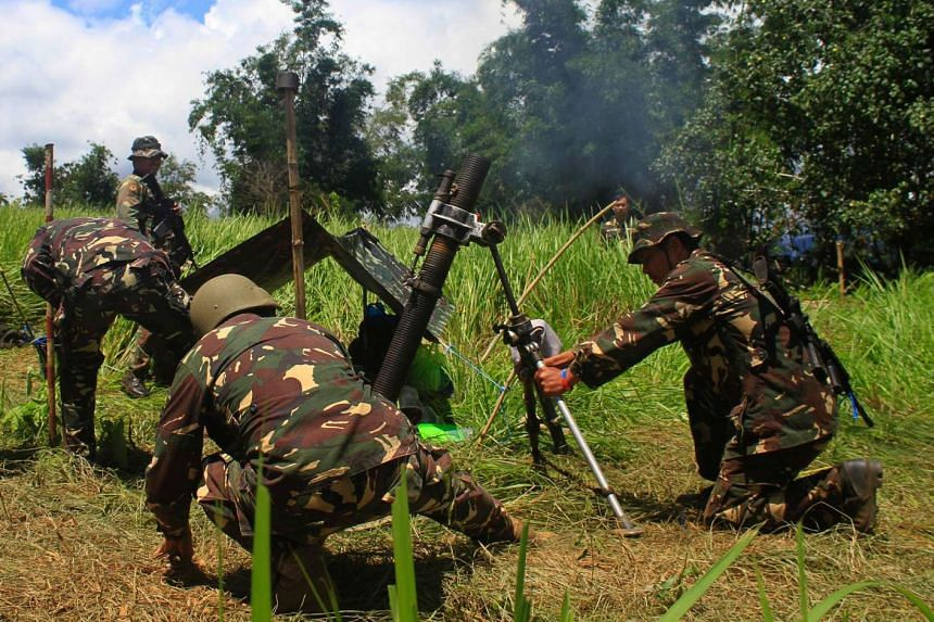 Philippine soldiers firing mortar rounds toward Islamic militant positions from Butig town, in the Philippines, on May 29, 2016.