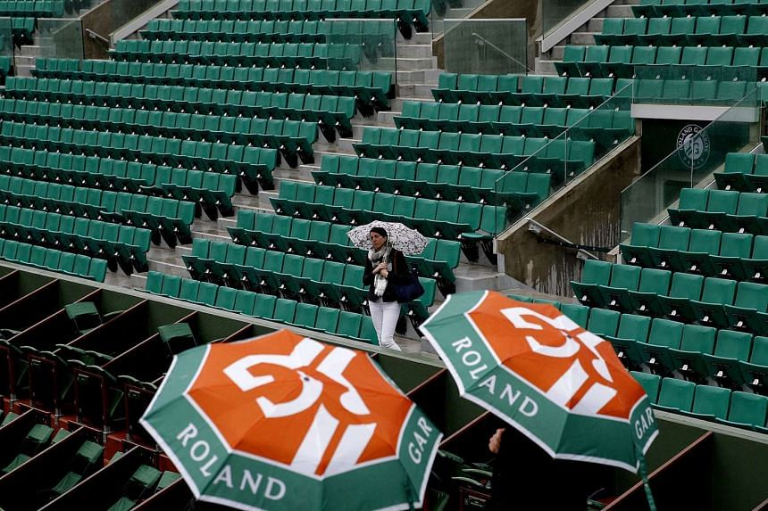 People wait in the stands of Court Philippe Chatrier as the start of day 9 is delayed due to rain at the French Open at Roland Garros, on May 30, 2016.