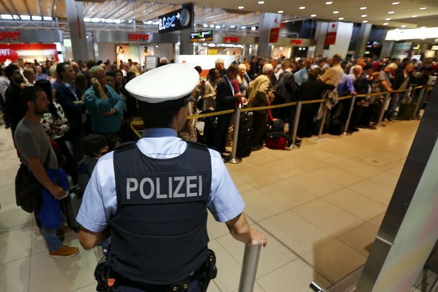 A police officer stands in front of passengers lining up at the entrance, following a security alert at Cologne airport, on May 30, 2016.