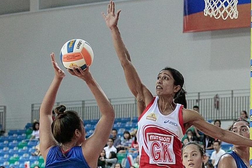 Singapore goal defender Premila Hirubalan (right) attempts to block a shot at the 2014 Nations Cup.