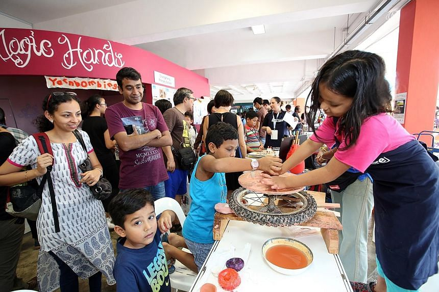 """A young participant showing visitors how to throw clay on her do-it-yourself pottery wheel during last year's Maker Faire. Children with a self-made """"city"""" created using recycled materials and LED lights during an Imagin8ors holiday camp last Decembe"""