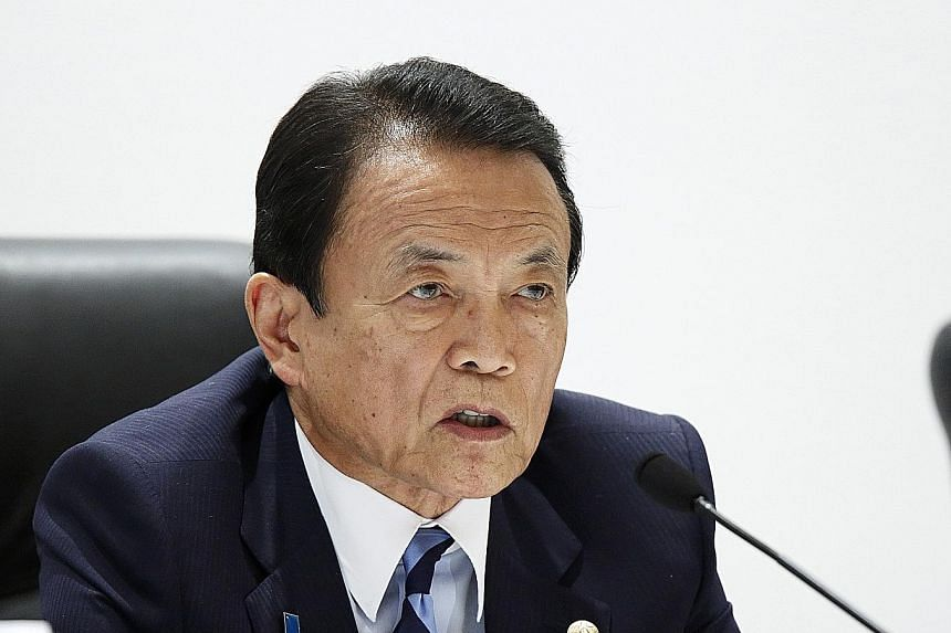 Mr Aso (left) made the remarks after Abe aide Hakubun Shimomura (right) said Japan might delay its sales tax hike for 2½ years from April 2017.