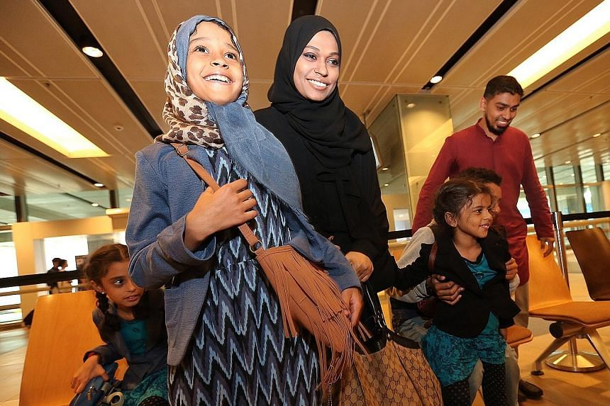 Madam Sherin (wearing black) with her children (from left) Iman, Afaaf, Wafaa and Ahmad (partially blocked) arriving at Changi Airport Terminal 1 in April last year. They had been evacuated from Yemen, where tensions were high with clashes between th