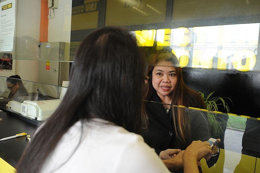 Mrs Ang (right) of Western Union had been trained to spot parcel scams and was able to prevent a customer from falling victim to one.