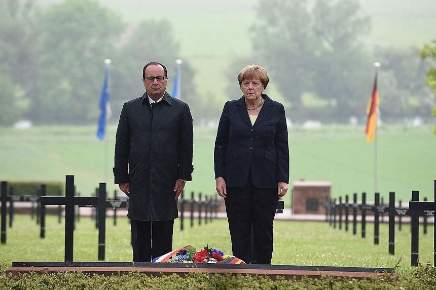Mr Hollande and Ms Merkel paying their respects at the German military cemetery in Consenvoye, in north-eastern France, where soldiers who died in the 1916 Battle of Verdun are buried.
