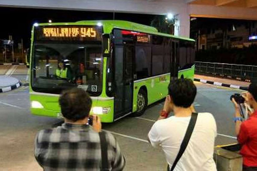 Bus spotters look on as the first Tower Transit bus arrives at Bukit Batok Bus Interchange.