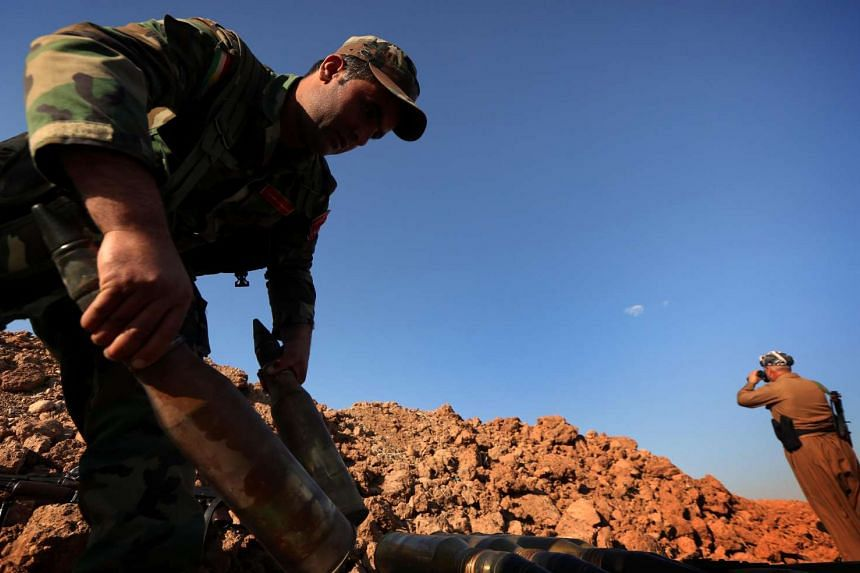 An Iraqi fighter prepares ammunitions near Hasan Sham village during an operation aimed at retaking areas from the Islamic State group on May 29.