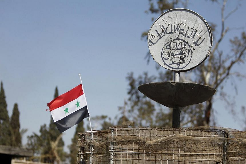 A Syrian national flag flying next to the Islamic State's slogan in the city of Palmyra, in Homs Governorate, Syria in this April 1 file photo.