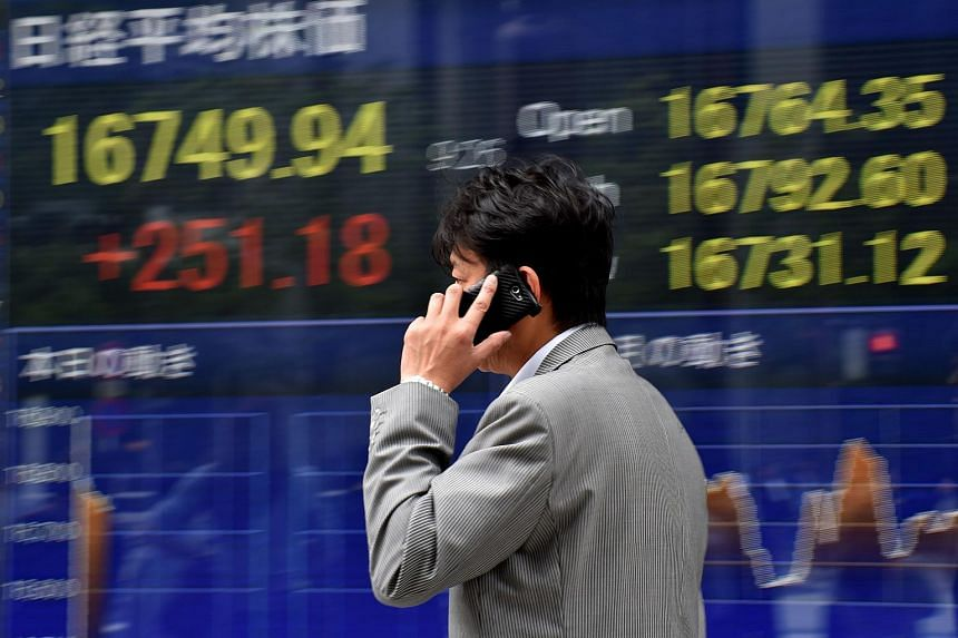 A pedestrian walks past a quotation board displaying the Nikkei index from the Tokyo Stock Exchange in Tokyo on May 25.