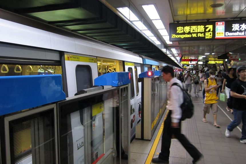 Commuters boarding and alighting from a Taipei Metro train.
