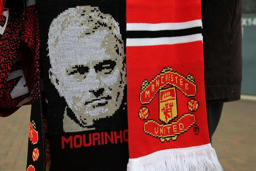 Scarves featuring the image of Manchester United's new Portuguese manager Jose Mourinho are displayed for sale outside Old Trafford.