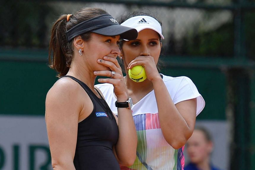 Martina Hingis (left) speaks to her teammate India's Sania Mirza during their women's double's match at the French Open.