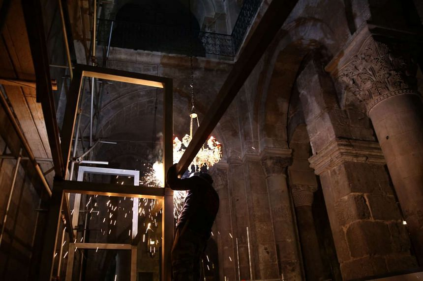 A worker welds scaffoldings at the Church of the Holy Sepulchre in Jerusalem's Old City ahead of the restoration of the Tomb of Jesus.