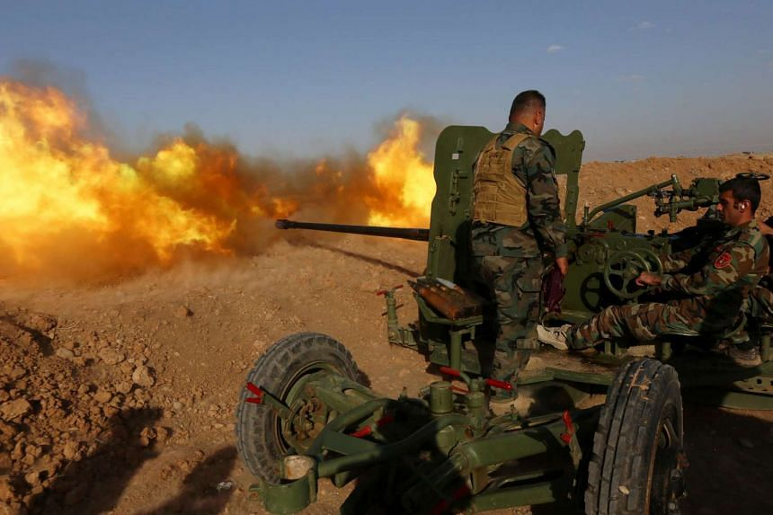 Iraqi Kurdish Peshmerga fighters fire an anti-tank cannon on the front line near Hasan Sham village, some 45 kilometres east of the city of Mosul, on Sunday.