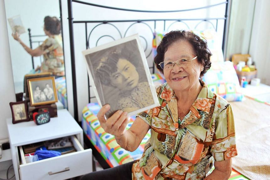 Madam Law with a picture of her younger self in her flat. The 87-year-old, who lives alone, says she is happy with her daily routine, which includes taking a stroll to the market.