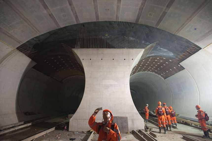 This file photo taken on May 06, 2009 shows a chinese journalist taking a picture of the 57-kilometre (35-mile) railway tunnel under construction in the Alps in Sedrun.