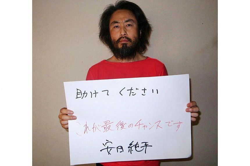 "Japanese freelance journalist Junpei Yasuda holding a piece of paper with a handwritten message in Japanese that says: ""Please help. This is the last chance. Jumpei Yasuda.""."