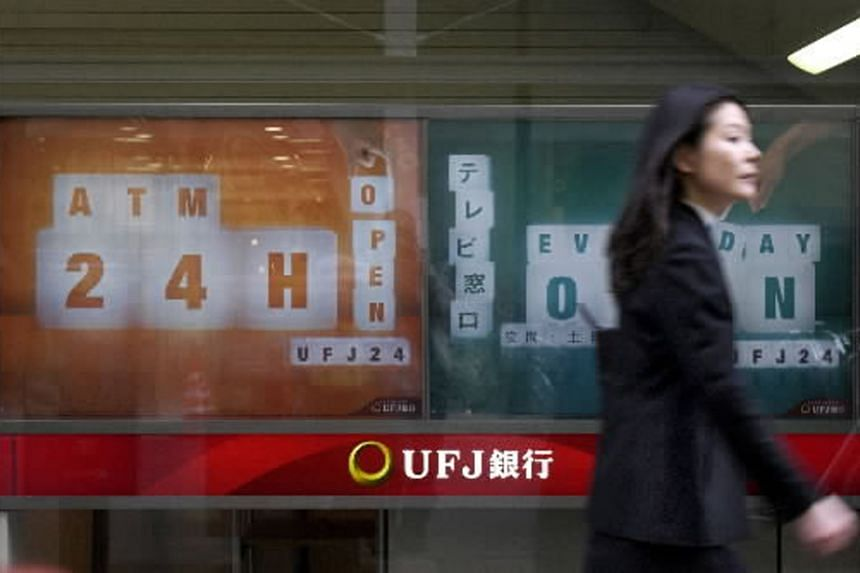 A woman walks past a sign announcing the start of UFJ Bank's 24-hour ATM service at a branch in central Tokyo, on March 31, 2004.