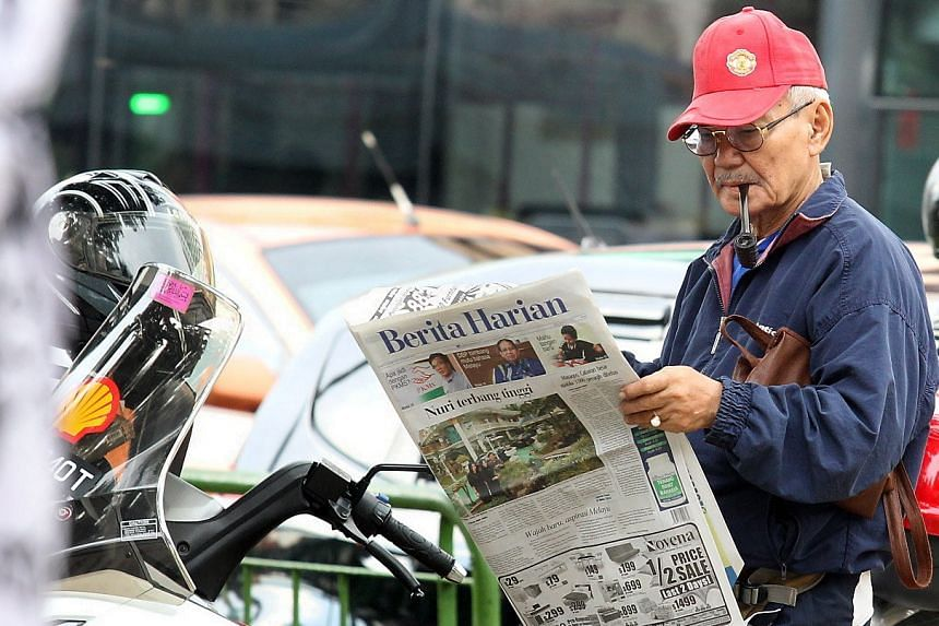 A man reading the Berita Harian newspaper at Geylang Serai on May 18, 2013.