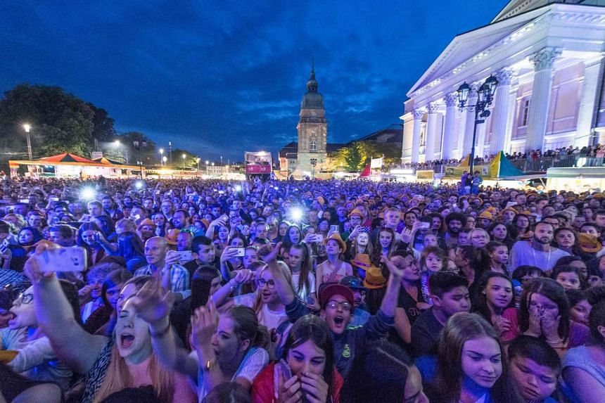 People enjoying an open air concert during the Schlossgrabenfest music festival in Darmstadt, on May 26, 2016. German police arrested three asylum seekers after 18 women made complaints of sexual assaults at the festival.