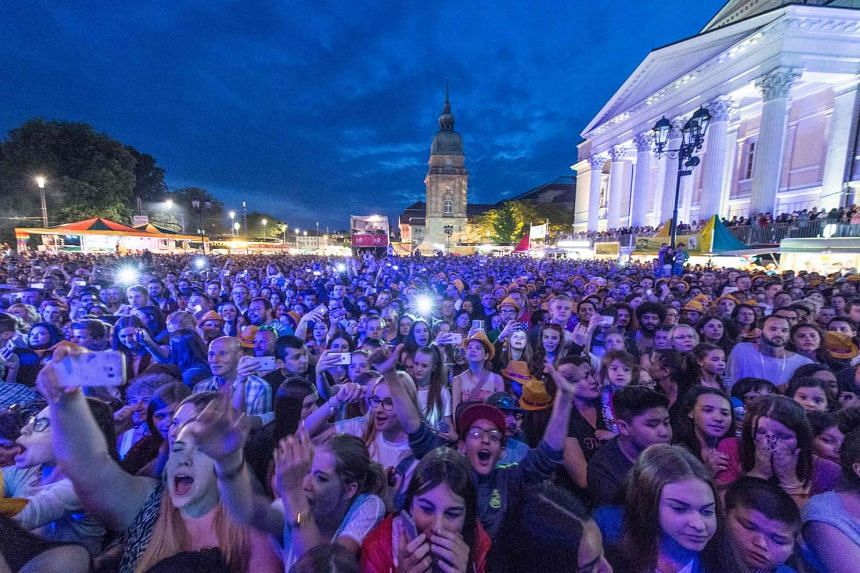 A photo taken on May 26, 2016 in Darmstadt, western Germany shows people enjoying an open air concert during the Schlossgrabenfest music festival.