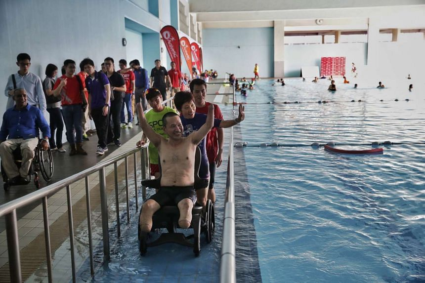 Ms Grace Fu helping an amputee out of the swimming pool via the ramp after launching the first Centre of Expertise for Disability Sports on May 31, 2016.