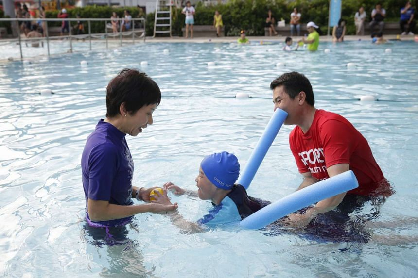 Ms Grace Fu in the swimming pool with nine-year-old Teo Choon Khang, after launching the first Centre of Expertise for Disability Sports on May 31, 2016.