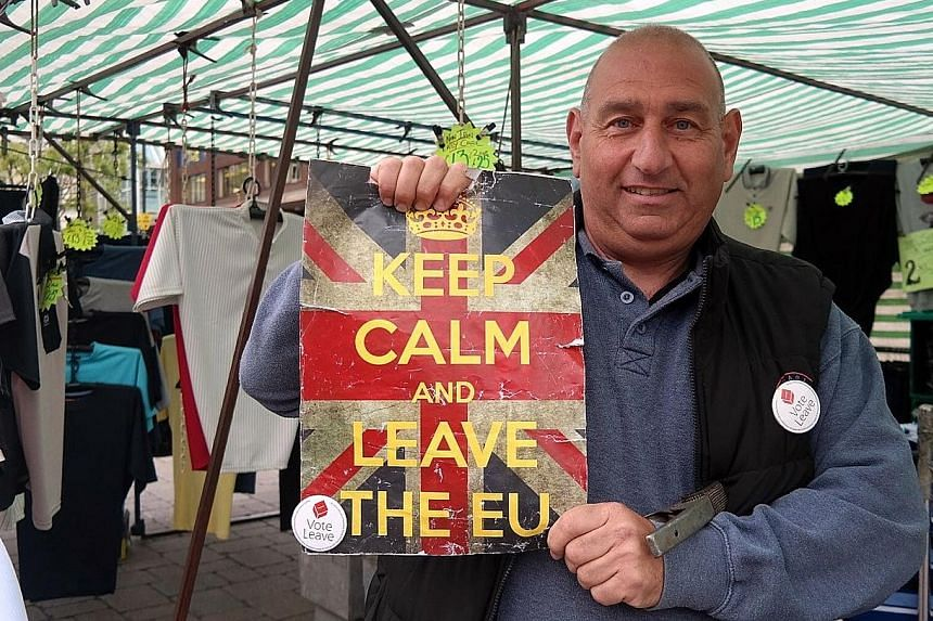 Mr Robert Reuben at his market stall in Romford in the borough of Havering. He says Britain's infrastructure can no longer cope with the inflow of immigrants. Posters encouraging people to register before June 7 to vote in the EU referendum on June 2