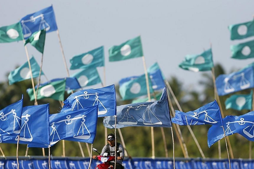 PAS and Barisan Nasional flags next to each other during the 2013 general election. PAS and Umno-led BN, once fierce rivals, are moving closer together as they seek to shore up their political support.