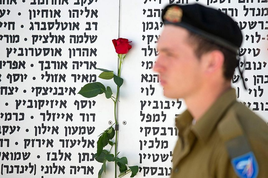An Israeli soldier observing a two-minute silence in front of a commemorative plaque honouring fallen soldiers at the Armoured Corps Memorial, following a ceremony to mark Remembrance Day on May 11 in Latrun, which lies between Jerusalem and Tel Aviv