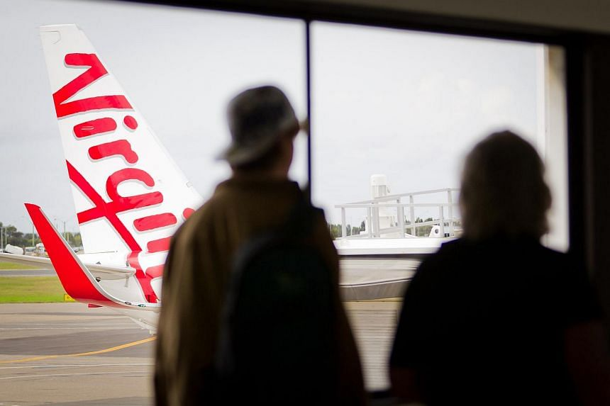Passengers walk past a Virgin Australia Holdings Ltd. Boeing 737 aircraft at the domestic terminal of Sydney airport.
