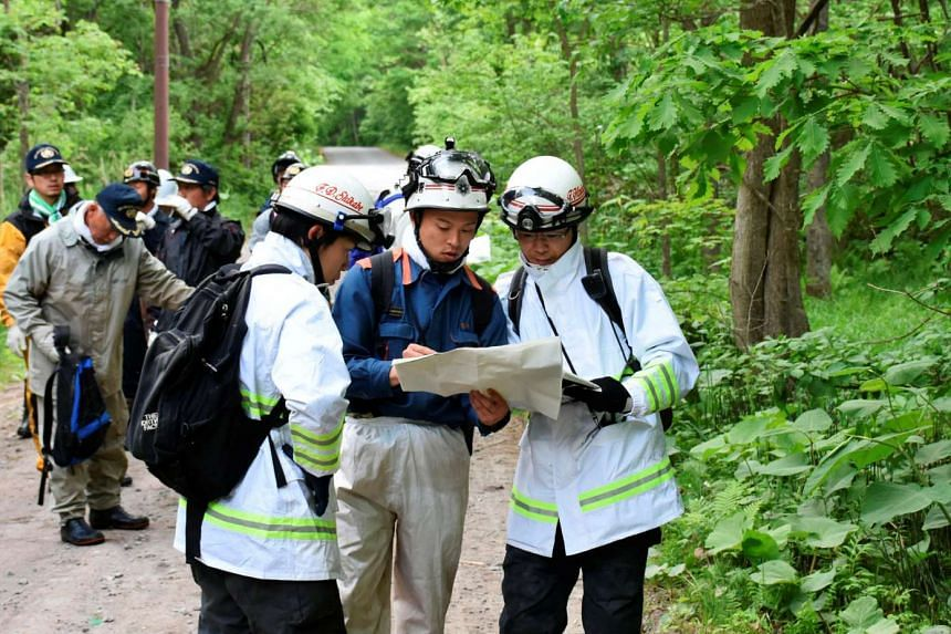 People search for a Japanese boy who went missing in Nanae town in Hokkaido, Japan, on May 30, 2016.
