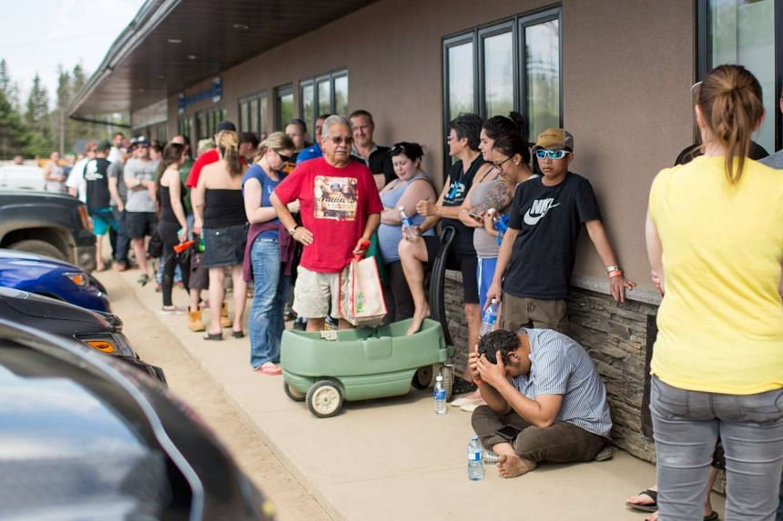Residents of Fort McMurray line up outside a grocery store after they were ordered to be evacuated due to a raging wildfire, in Anzac, Alberta, Canada on May 4. They are unable to return now due to contamination.