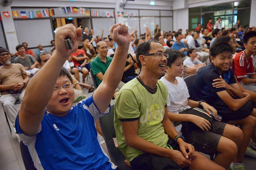 Roy Cheong (left) reacts to Luis Suarez's first goal for Uruguay at the live screening of World Cup match between Uruguay and England at the Bedok Community Centre, on June 20, 2014.