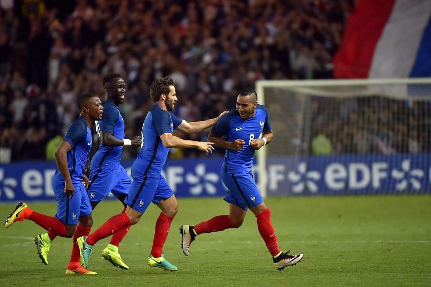 France's forward Dimitri Payet (right) celebrates with his teammates after scoring a goal during the International friendly football match between France and Cameroon.