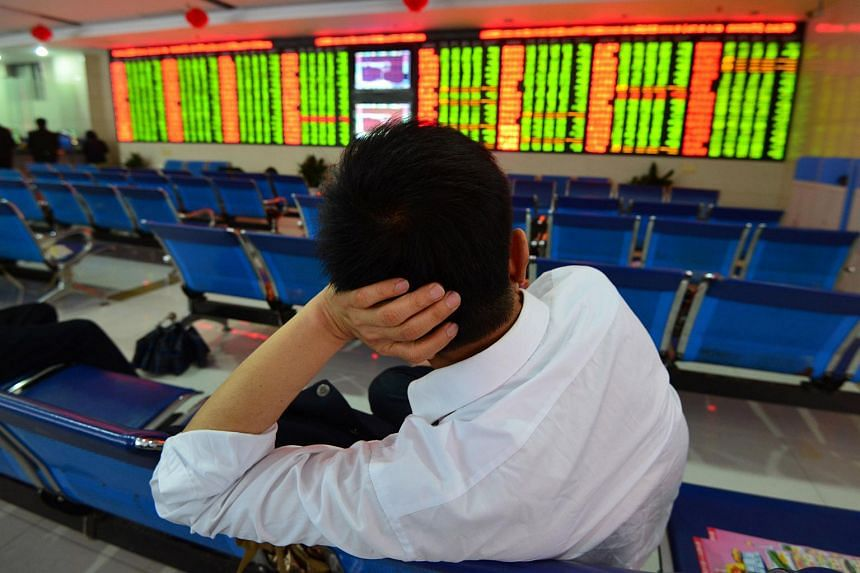 An investor sits in front of a screen showing stock market movements at a securities firm in Fuyang, China.