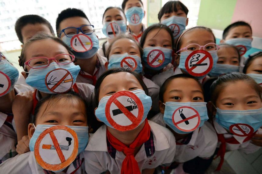 Chinese pupils wearing masks with no smoking signs to support World No Tobacco Day at a primary school in Handan, Hebei province, on May 30, 2016.