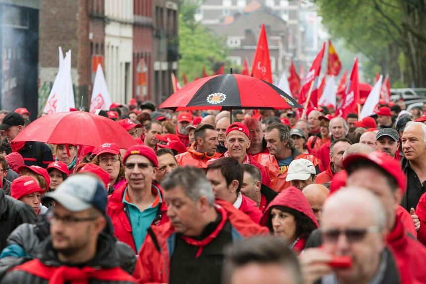 Members of CGSP, Belgian public sector workers's union, hold flags as they march during a protest against the government's austerity plans on May 31, 2016.