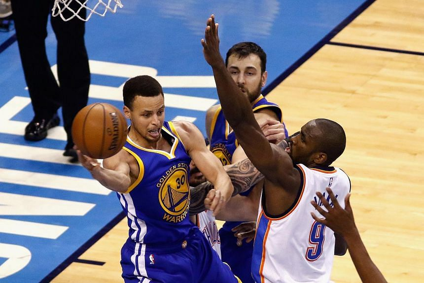 Stephen Curry (left) of the Golden State Warriors passes the ball against Serge Ibaka (right) of the Oklahoma City Thunder.
