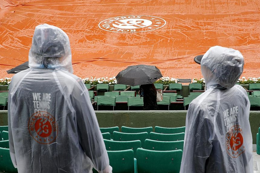People wait in the stands of Court Philippe Chatrier as the start of day 9 is delayed due to rain at the French Open tennis tournament.