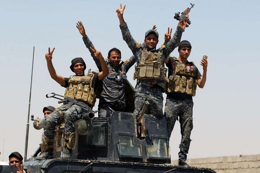 Pro-government forces fighters celebrate, as they take part in a major assault to retake the city of Fallujah from ISIS.