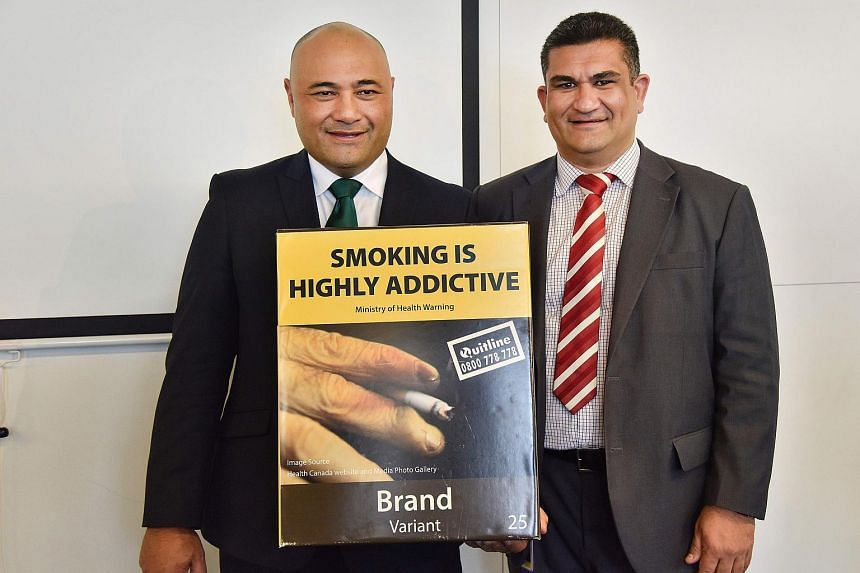 New Zealand Associate Health Minister Sam Lotu-Iiga (left) and Wellington City councillor Paul Eagle hold the mock-up of the new plain cigarette packaging during an announcement in Wellington.