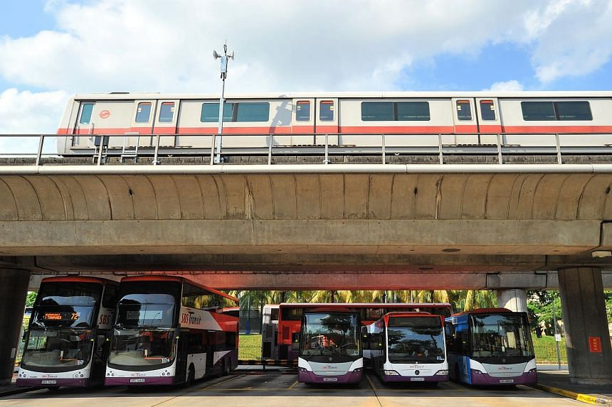 SBS buses parked under the SMRT track while an SMRT train passes by the Yio Chu Kang bus interchange on July 21, 2014.