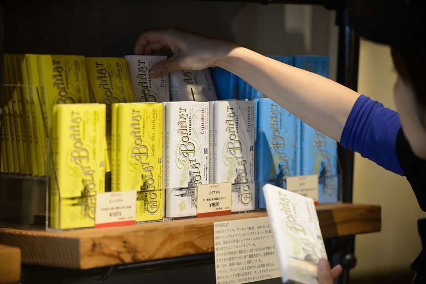 An employee arranging packages of artisan chocolate bars at Cacao Store, a specialist chocolate store, in Tokyo.