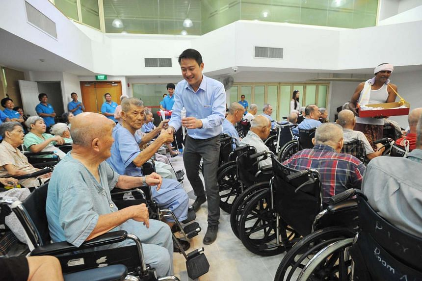 Dr Lam Pin Min, Minister of State for Health, mingles with residents of Ling Kwang Home for Senior Citizens while helping to distribute kacang puteh before the movie screening of Long Long Time Ago.