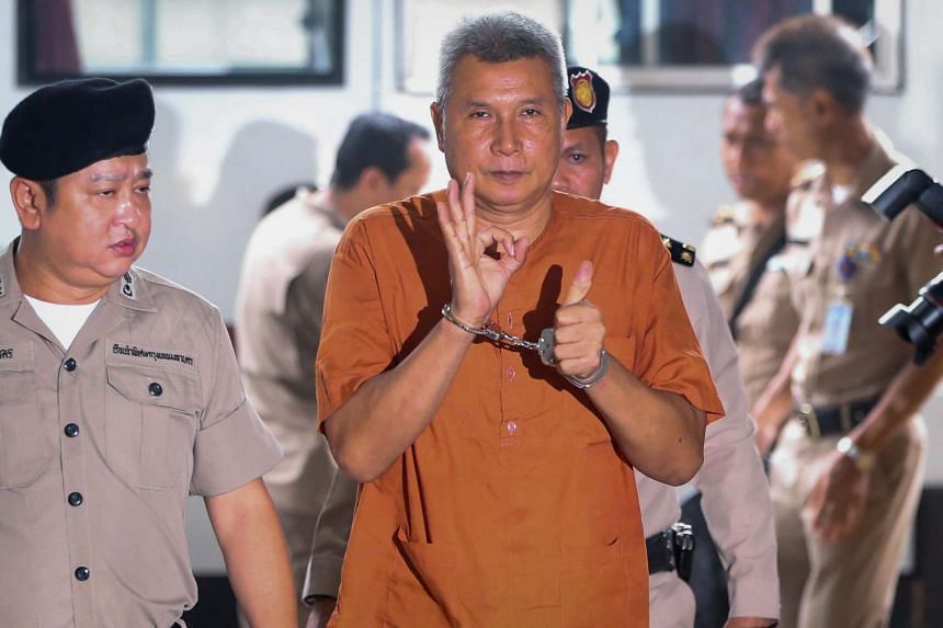 Singer and actor Thanat Thanawatcharanont is escorted by police officers as he arrives at a criminal court in Bangkok, Thailand, on June 1, 2016.