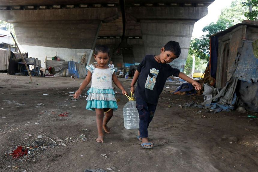 Children carry a drinking water container after filling it from a municipal tap under a flyover at a slum area in Kolkata, India on May 26, 2016.