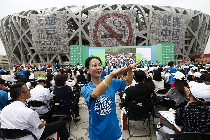 An anti-smoking advocate dancing at the Bird's Nest stadium to mark World No Tobacco Day in Beijing yesterday. According to the WHO, China is the world's largest producer and consumer of tobacco products. More than 300 million people in the country a