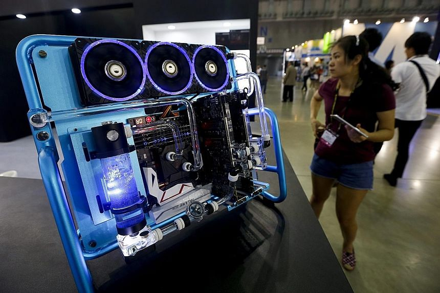 A visitor checking out a computer with a liquid cooling system at Taipei's Computex expo - the largest computer trade show in Asia - yesterday. The five-day event, which ends on Saturday, gathers 1,602 exhibitors from 30 countries occupying 5,009 boo